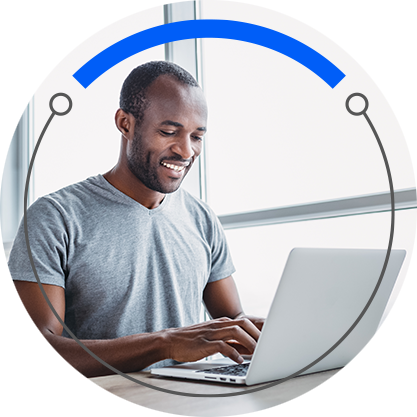 A man works on his laptop while smiling